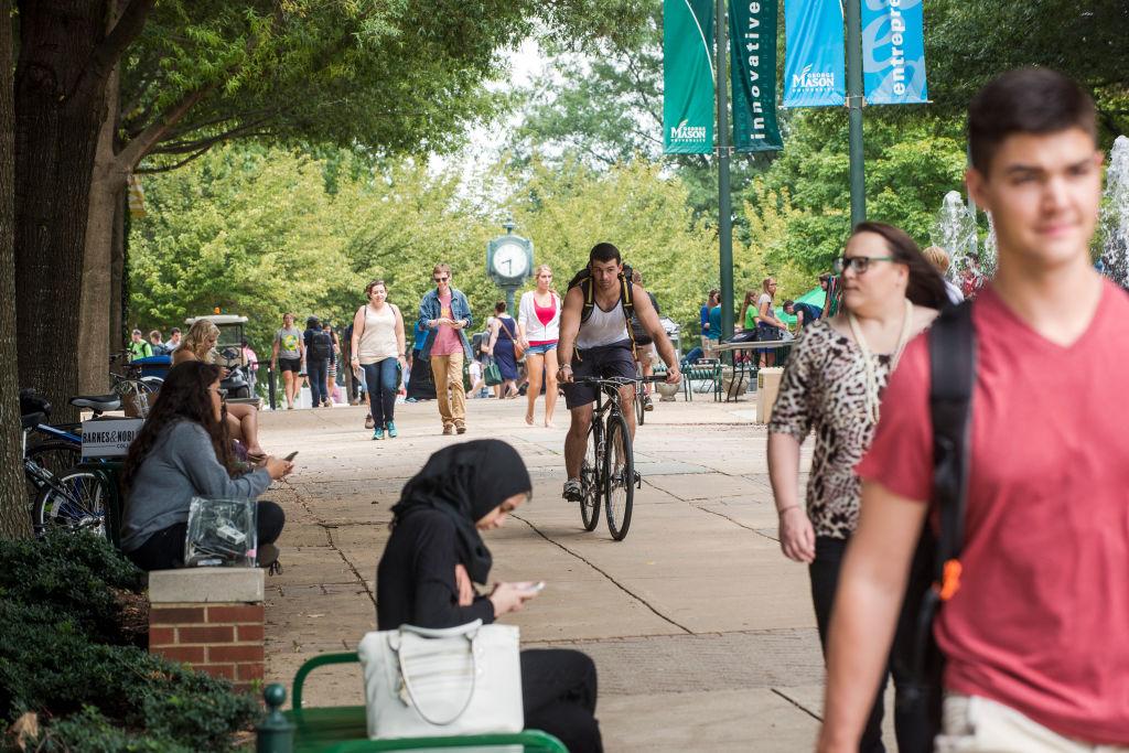 Mason students walk through the Fairfax Campus between classes
