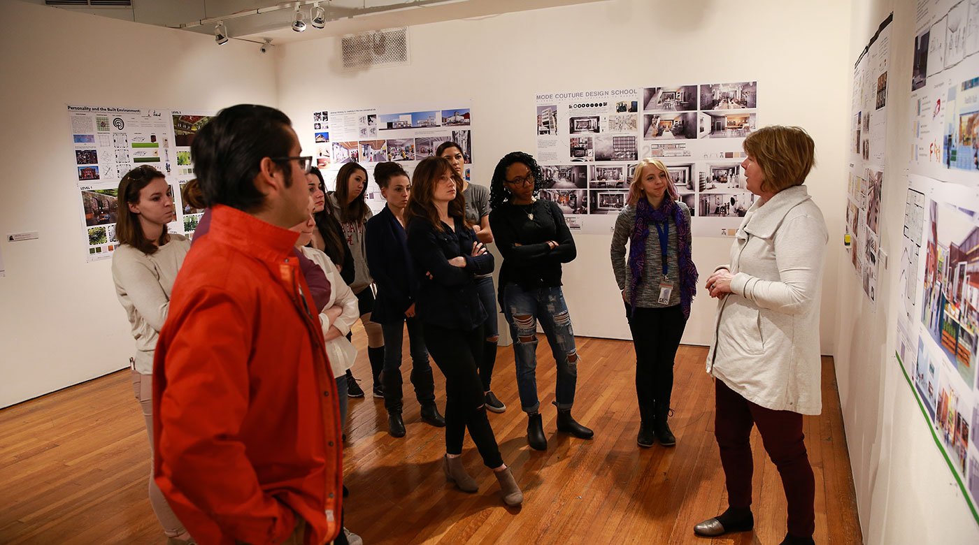 Students gather with their professor at a local art gallery.