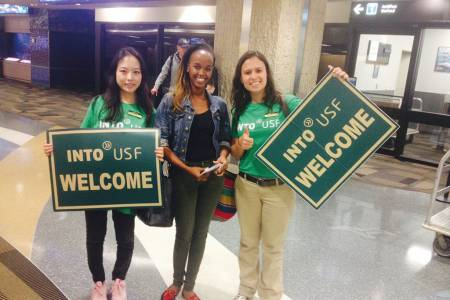 A new student is greeted by INTO staff holding INTO USF welcome banners at Tampa Airport