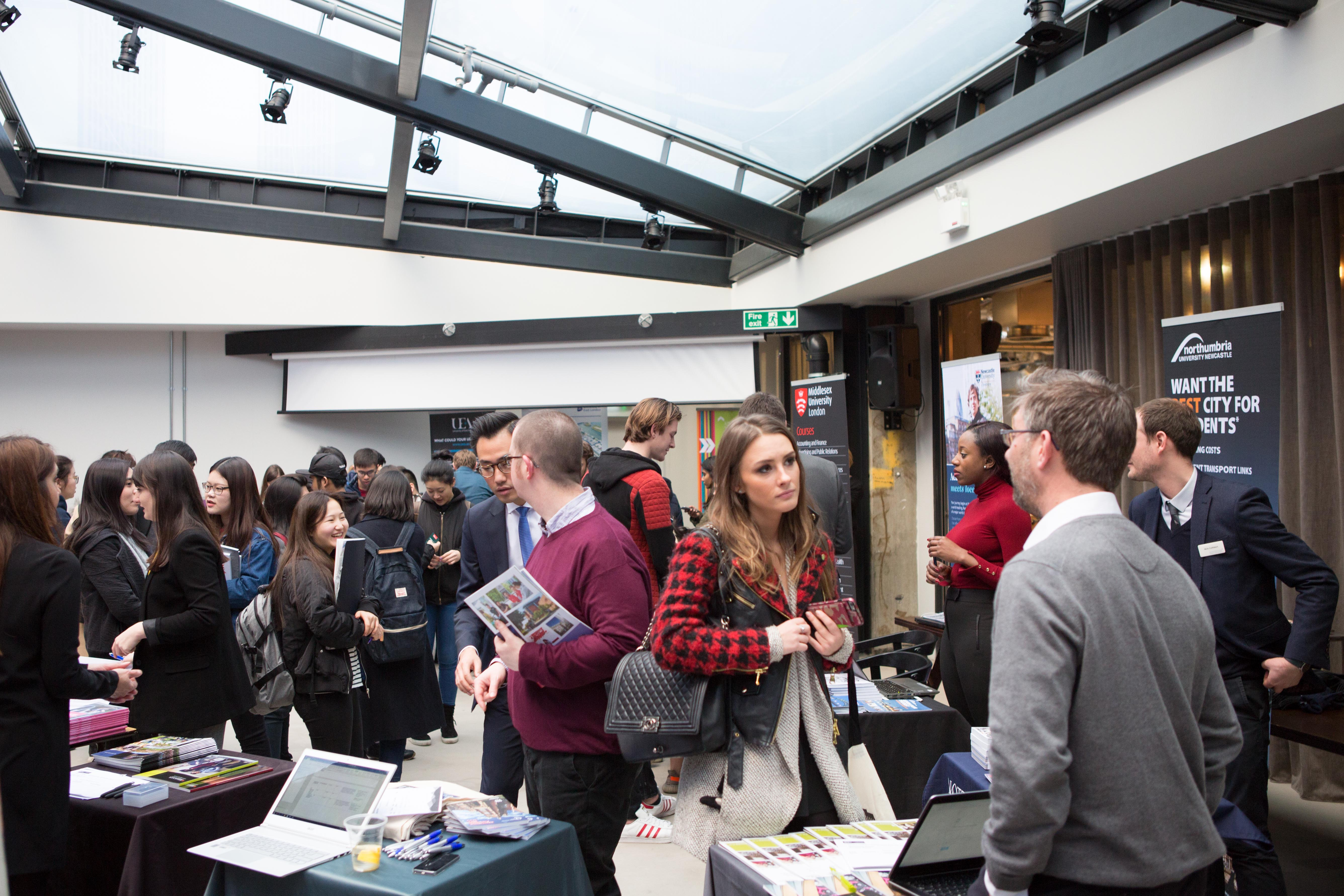Image of room with University exhibition stands and international students talking to people about the universities