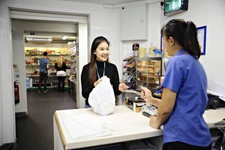 Student buying food from staff at the on-site shop and takeaway café