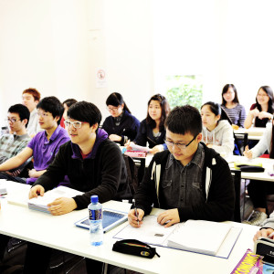 A class of INTO international students using textbooks and iPads to study