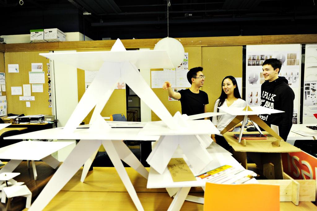 Built Environment students looking at a paper model
