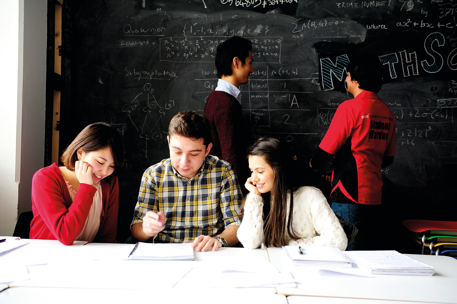 International students working in an UEA Classroom with blackboard