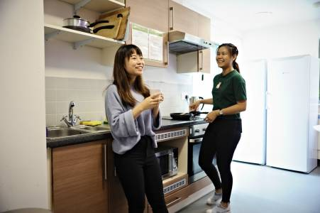 International students talking in shared kitchen in INTO University of Exeter student residences