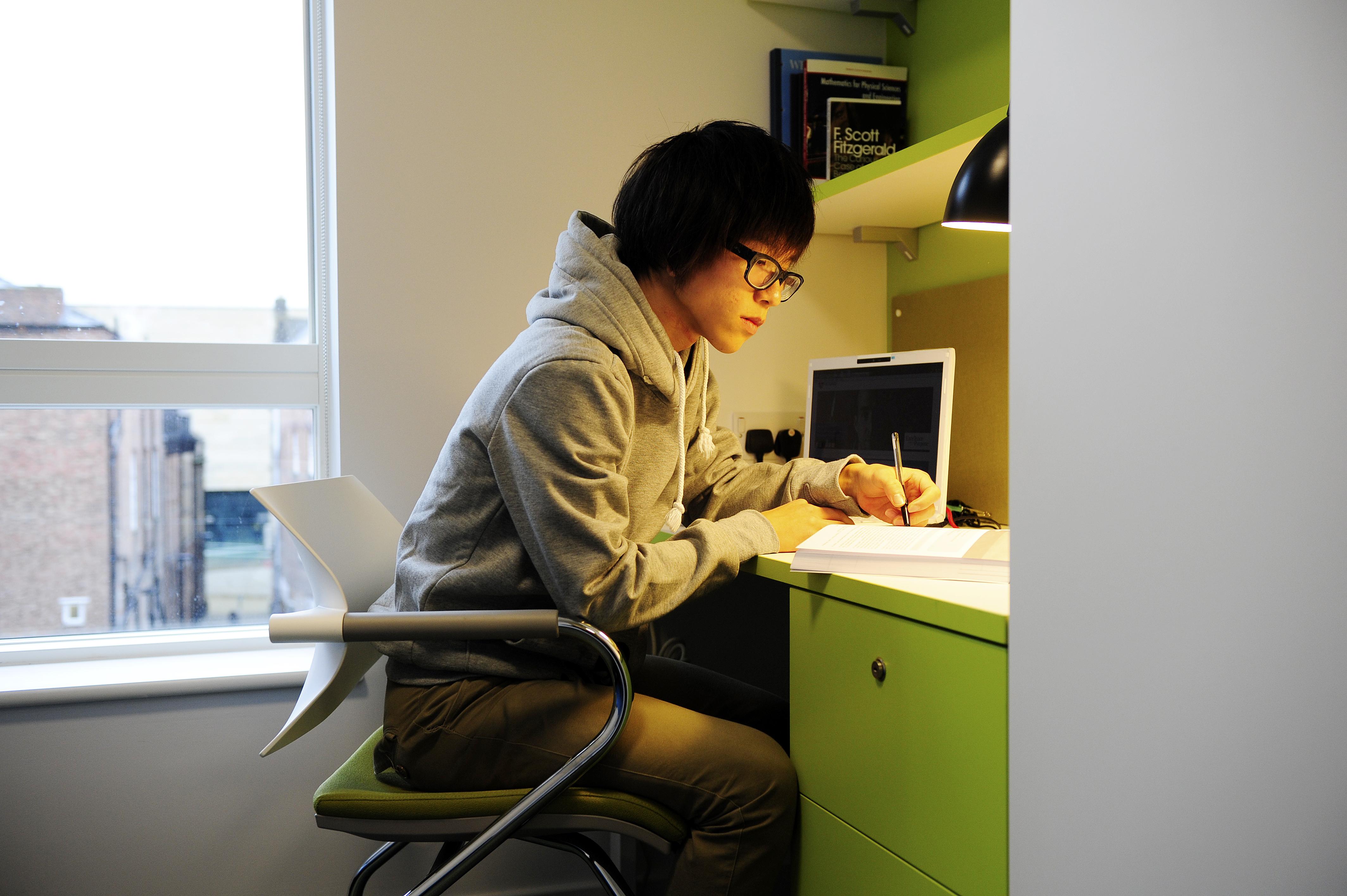 طالب يدرس في سكن طلاب مركز INTO