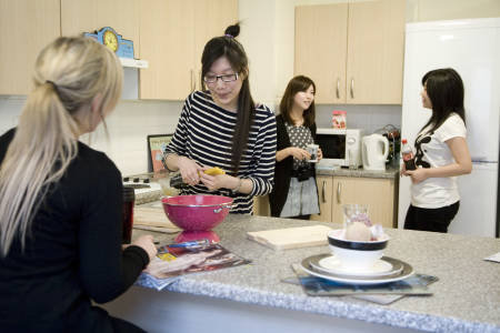 International students cooking in Liberty Park shared kitchen at INTO Glasgow Caledonian University