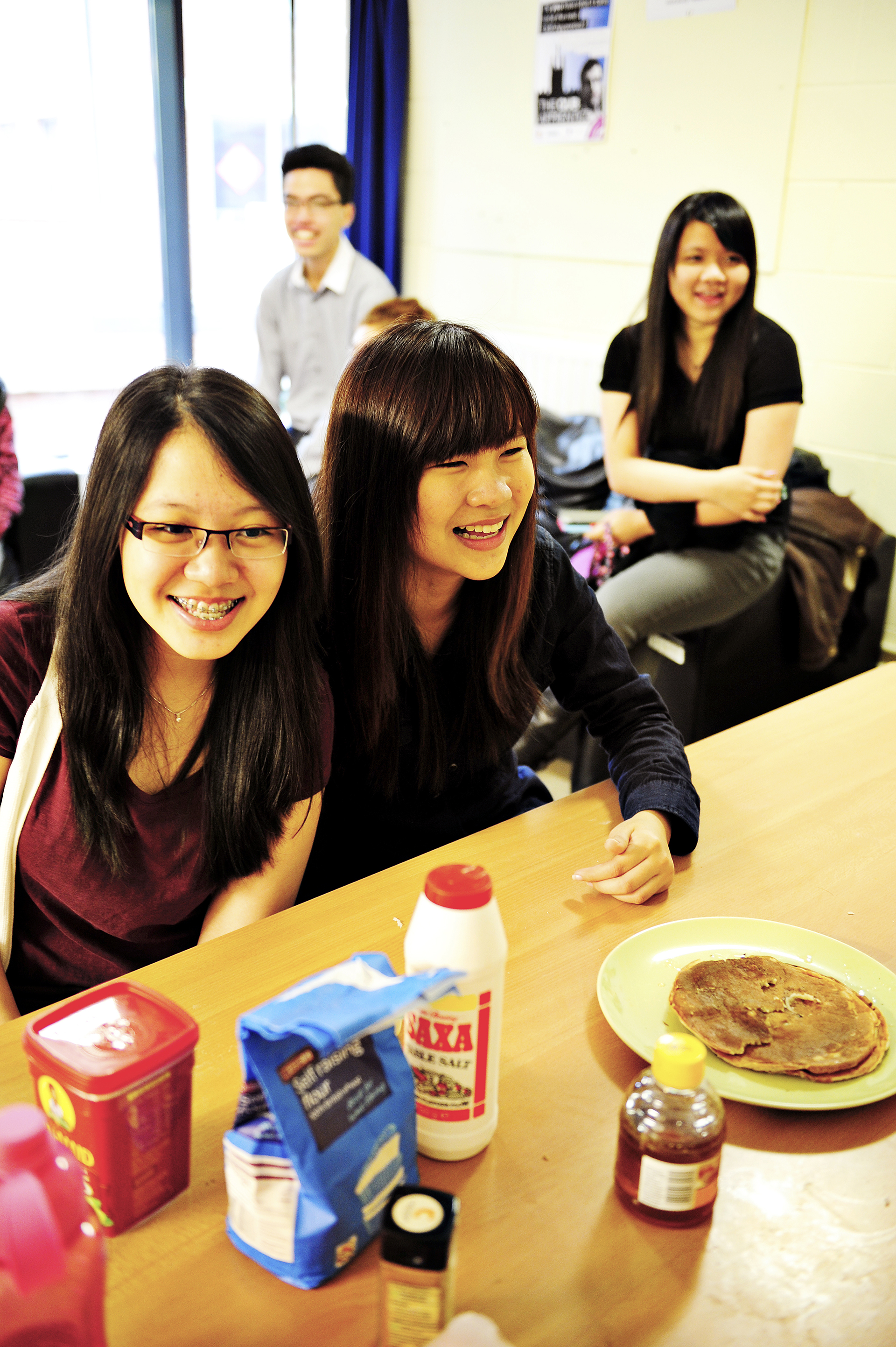 International students enjoying a meal together in shared kitchen area in student accommodation
