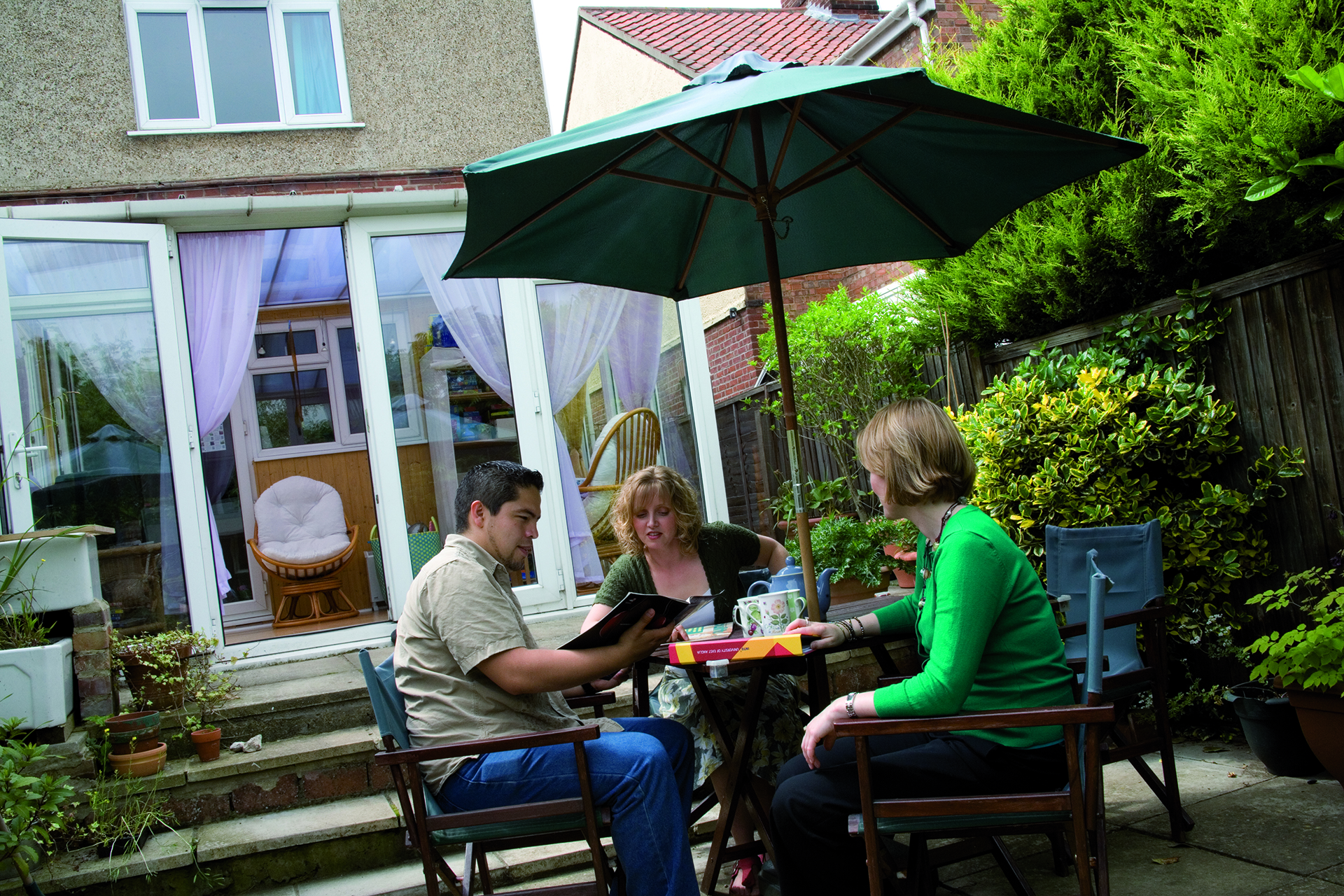 A student and their homestay accommodation hosts sitting at a table in a garden