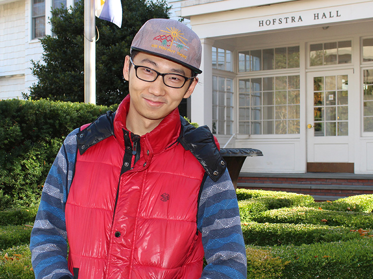 Hofstra male student posing for camera outside building hall