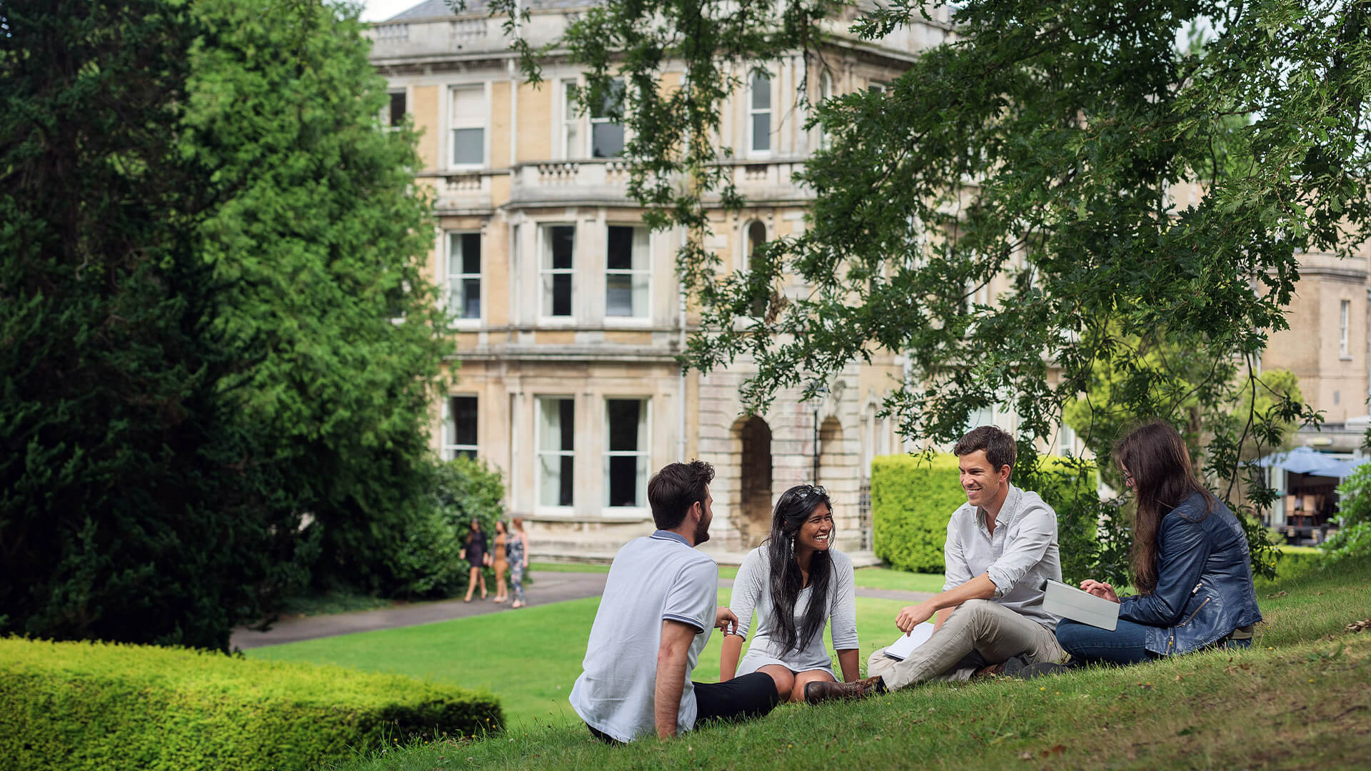 Students studying outside on the grass at University of Exeter campus