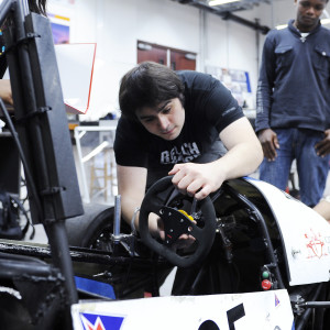 Four engineering students assemble the steering wheel on a kit car
