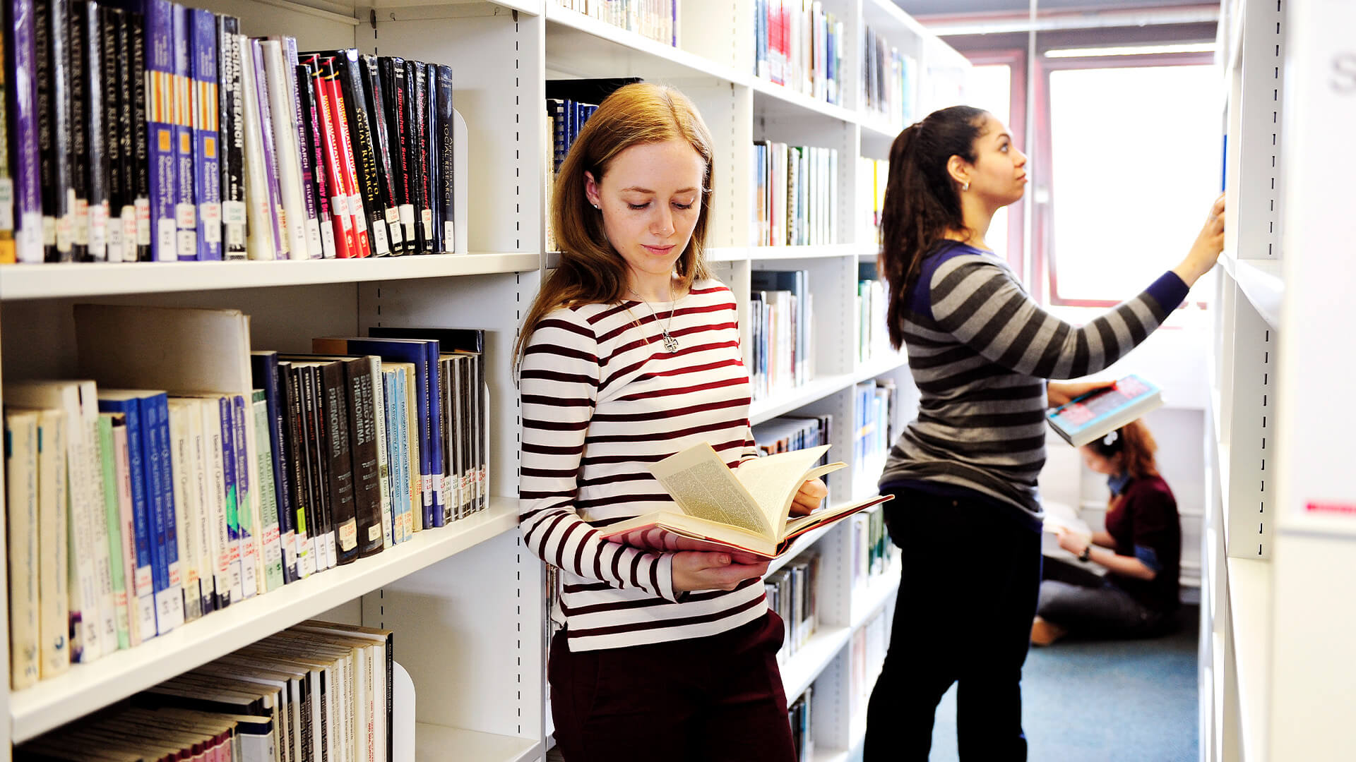 International student browsing through books in the City, University of London library