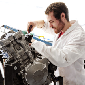 Engineering student in lab coat works on engine at University of Exeter