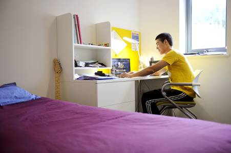 Student sitting in bedroom at INTO University of Exeter