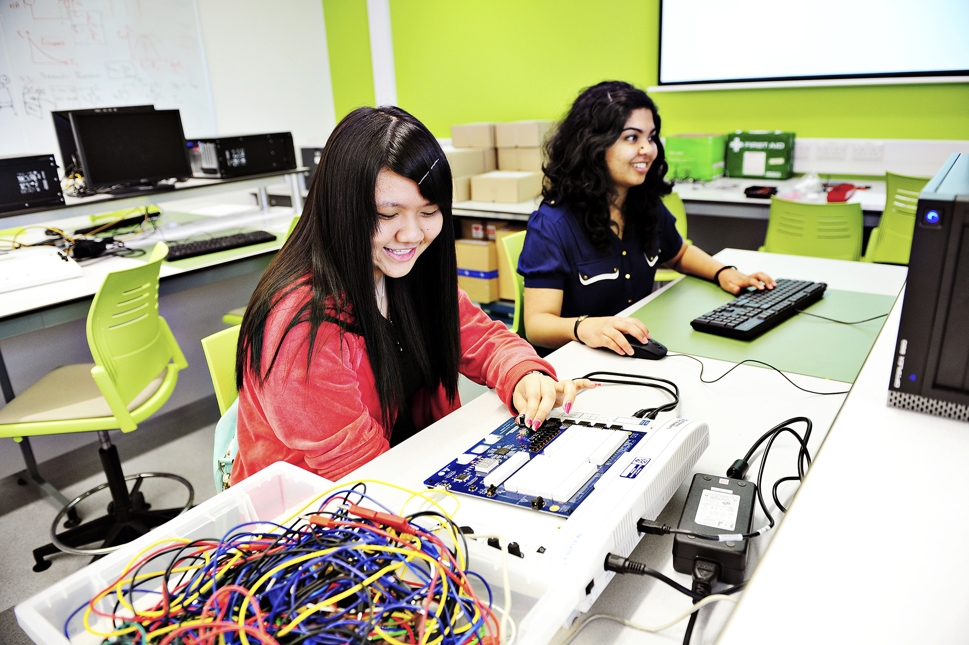 Two INTO international students in an electronics lab, one studying on a computer, the other on an electrical unit