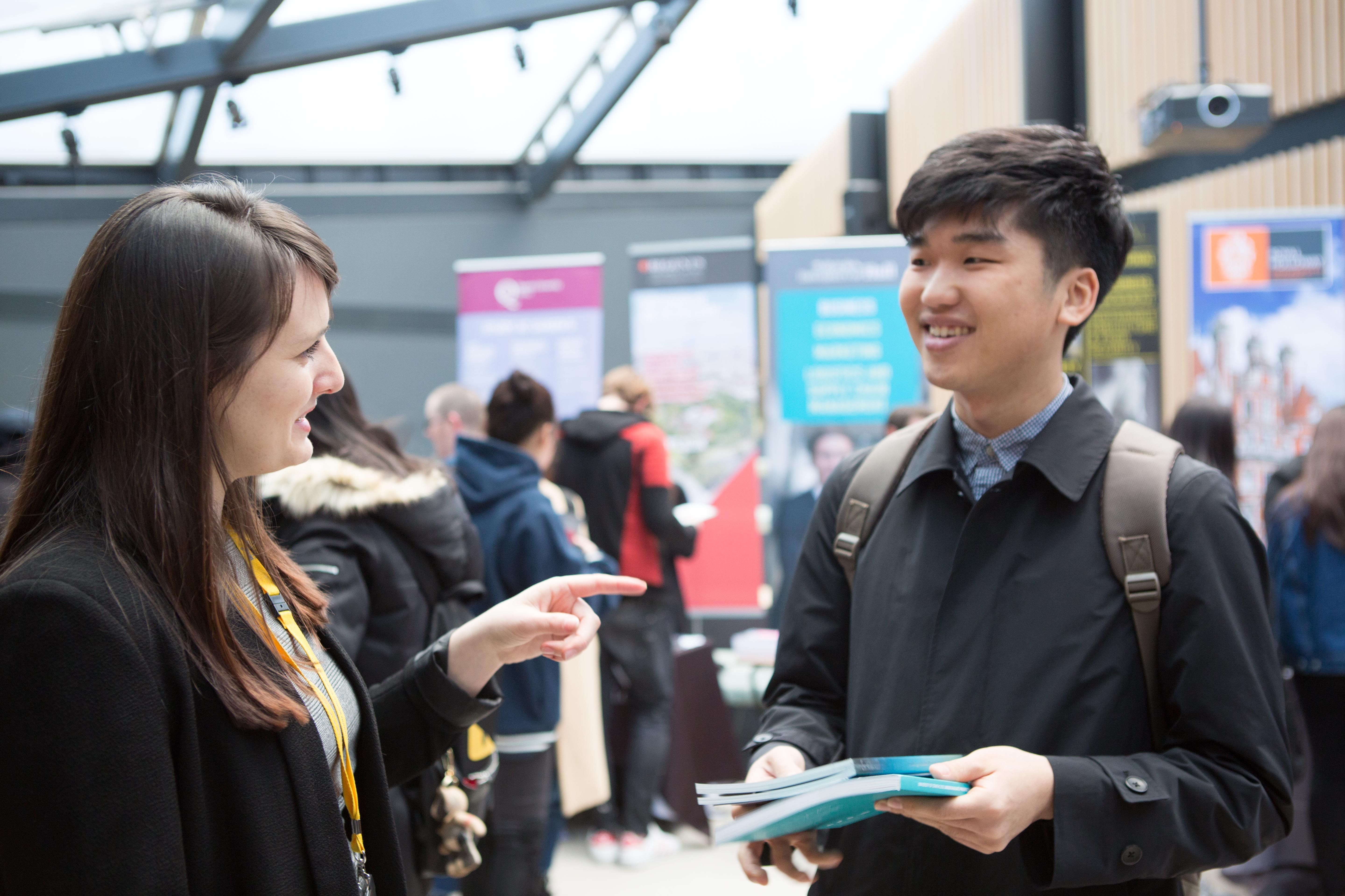 International student speaking to representative at University exhibition stand