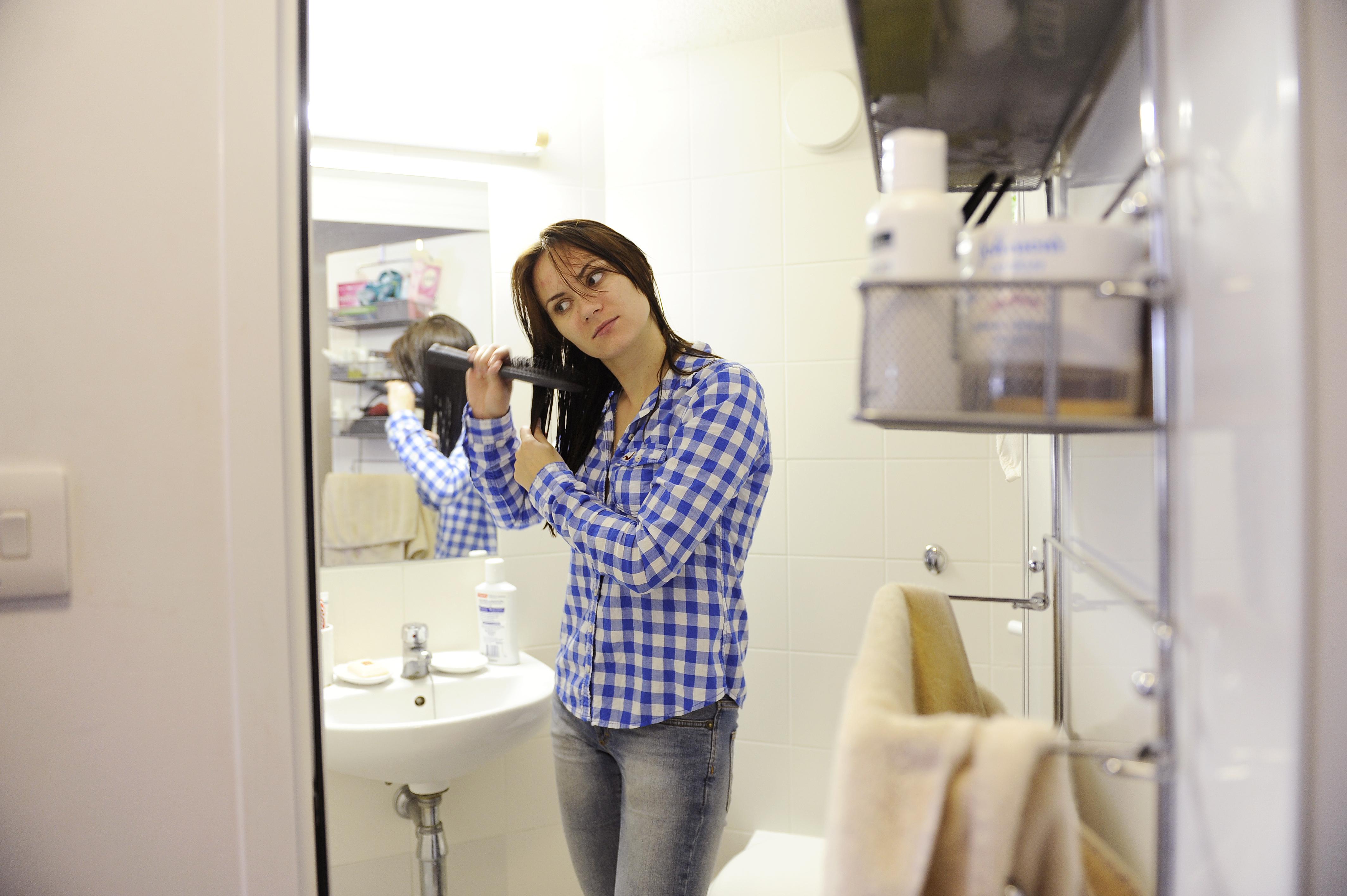 学生在INTO UEA中心学生宿舍的套间卫浴里整理头发