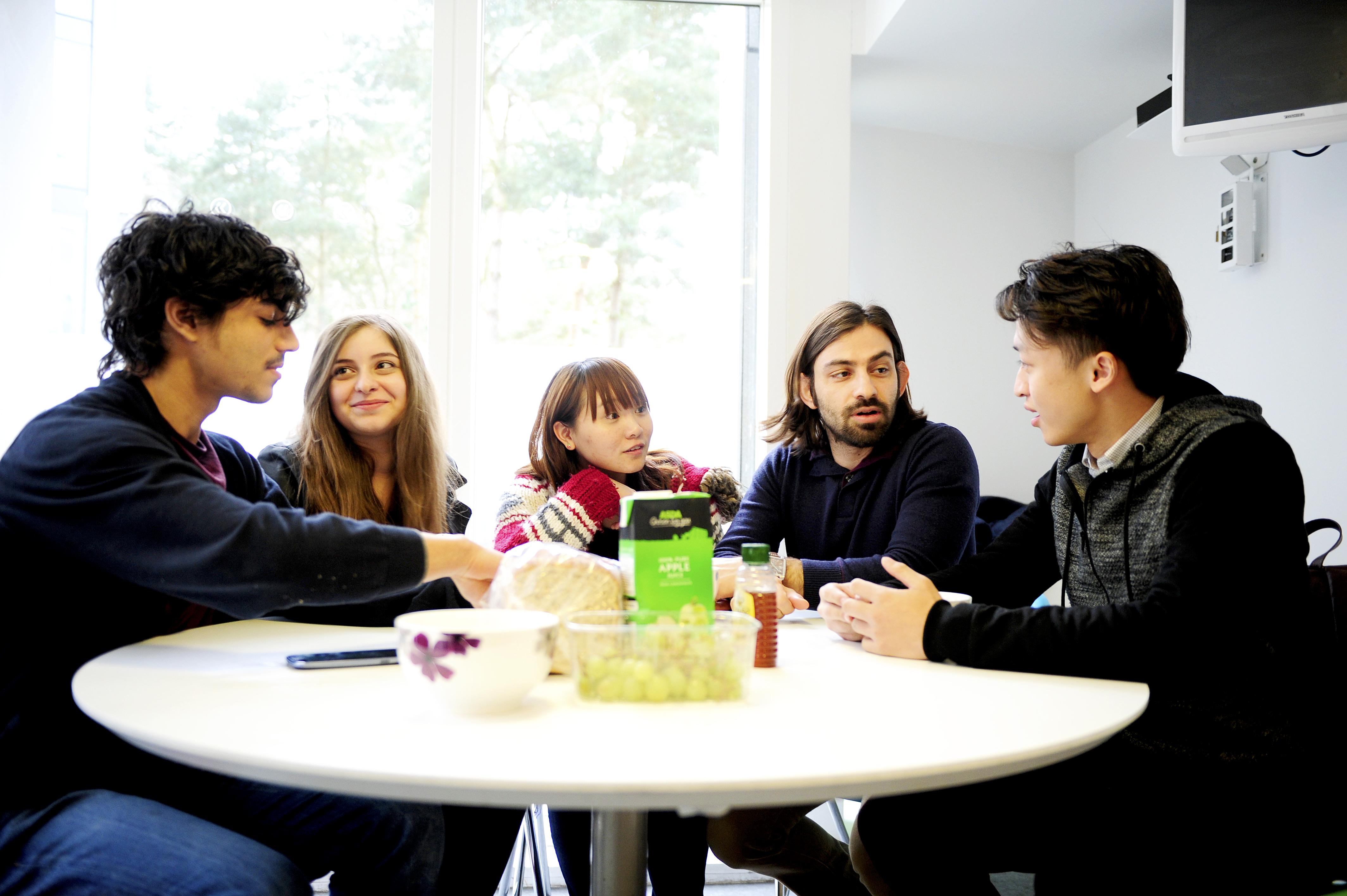 学生在INTO UEA中心学生宿舍的厨房里开展社交活动