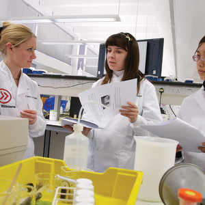 Students in lab coats with equipment in lab