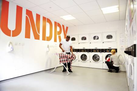 International students using shared laundry facilities in the Scape East building