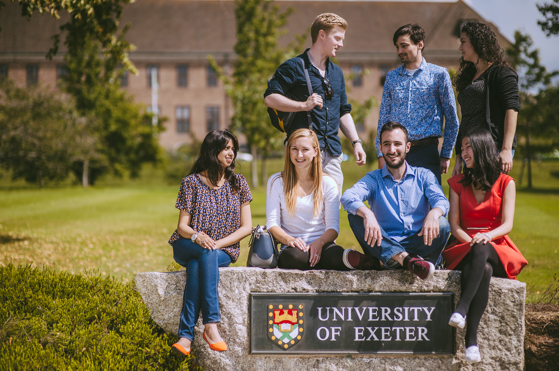 International students standing outside by the University of Exeter sign