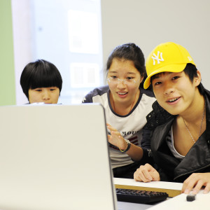A group of three INTO International students are gathered around a desk-integrated computer