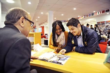 国际学生在INTO中心接待前台浏览大学手册