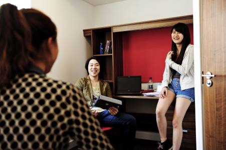 International students in Craft bedroom with laptop