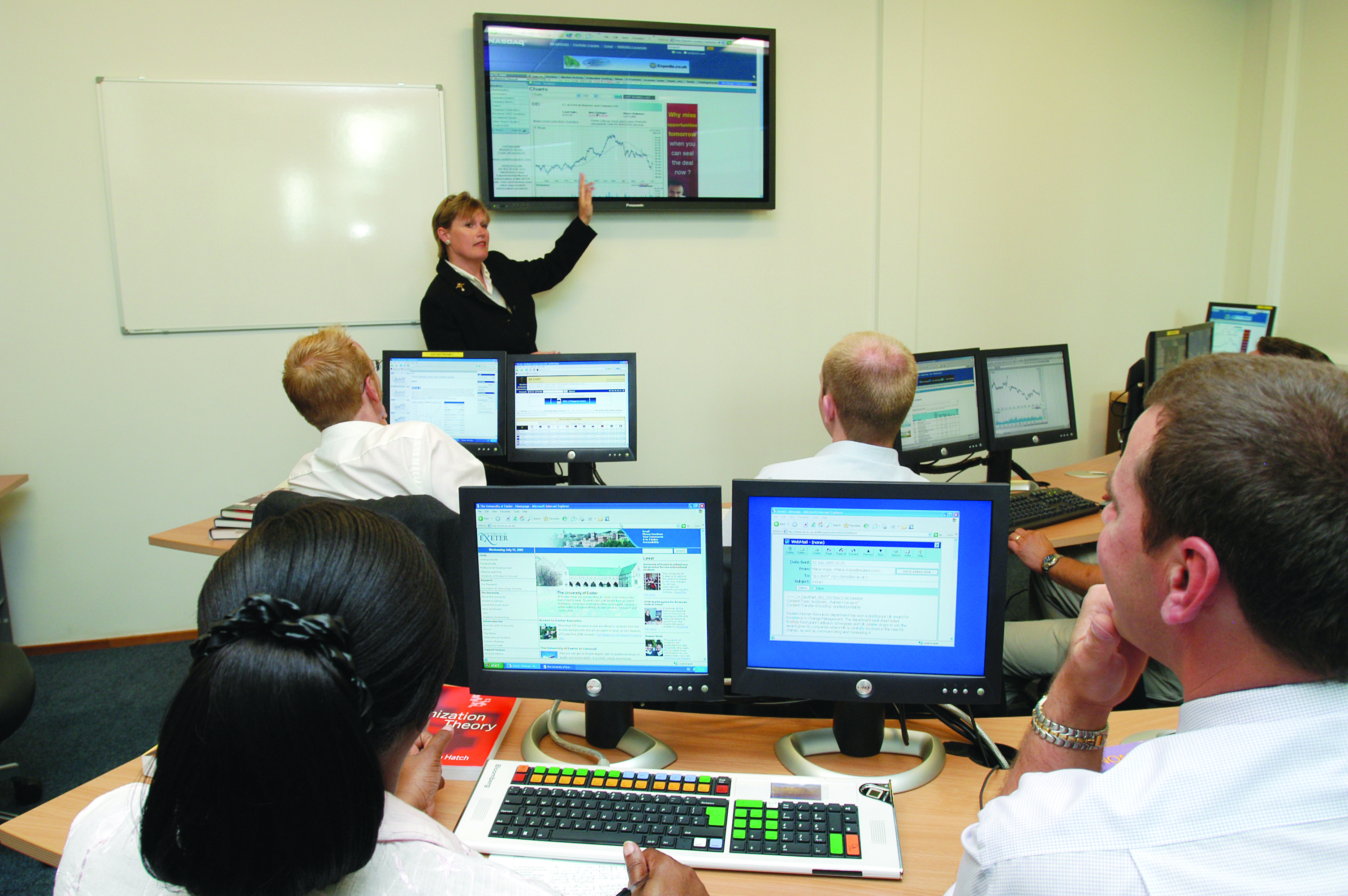 Teacher explains financial graph to students in University of Exeter classroom