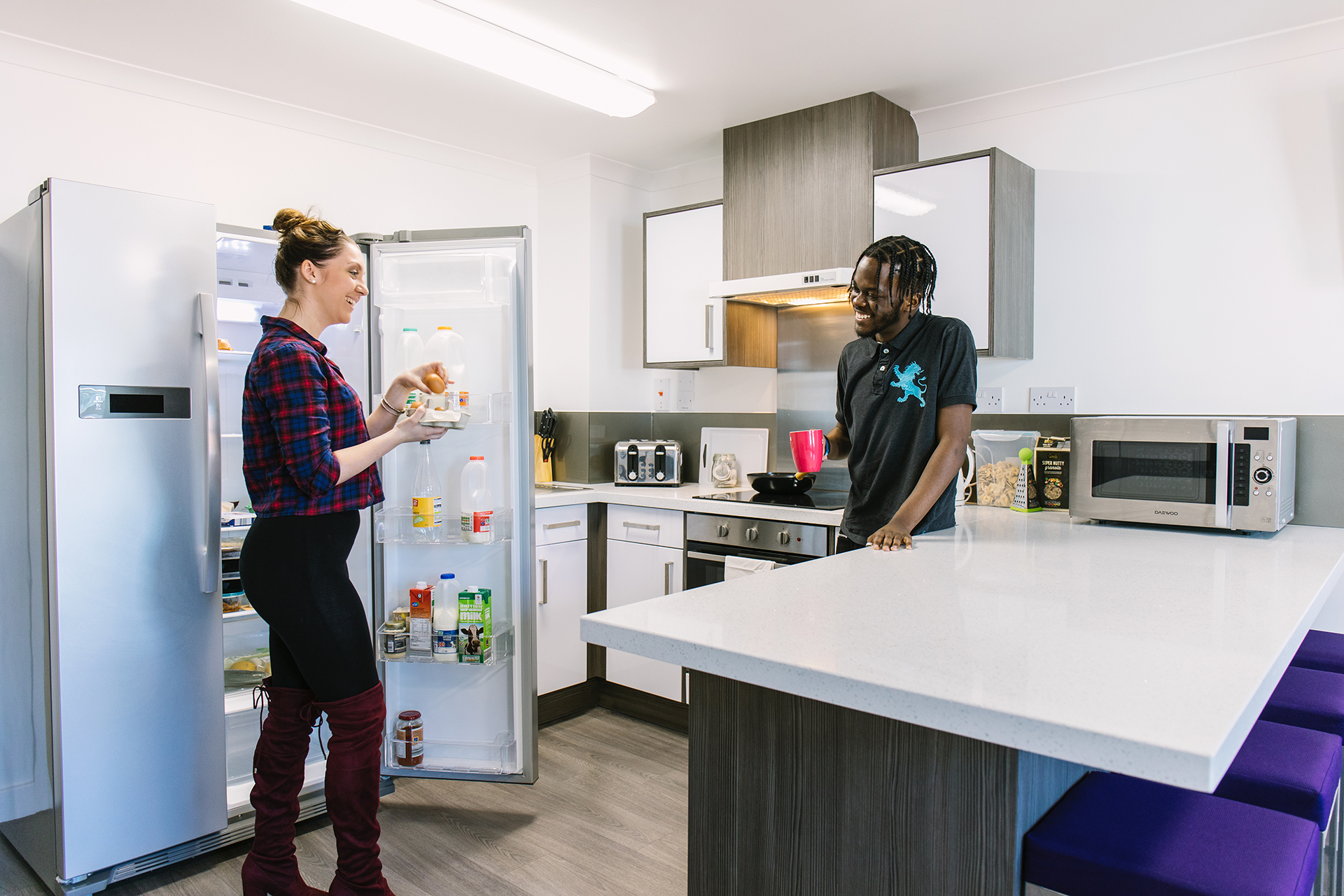 Students talking and eating in INTO Manchester shared kitchen