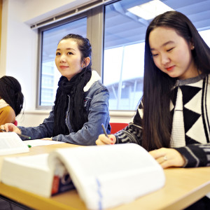 INTO international students learning in a classroom from textbooks