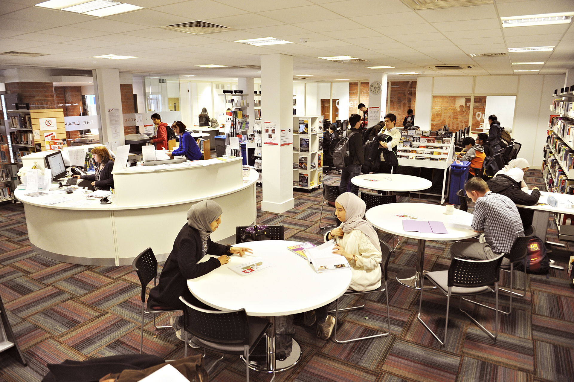 International students working in Learning Resource Centre with help desk