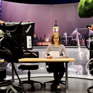 Student sits behind a news desk with a background of London behind her