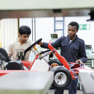 Two students work on a go kart in a mechanic's garage
