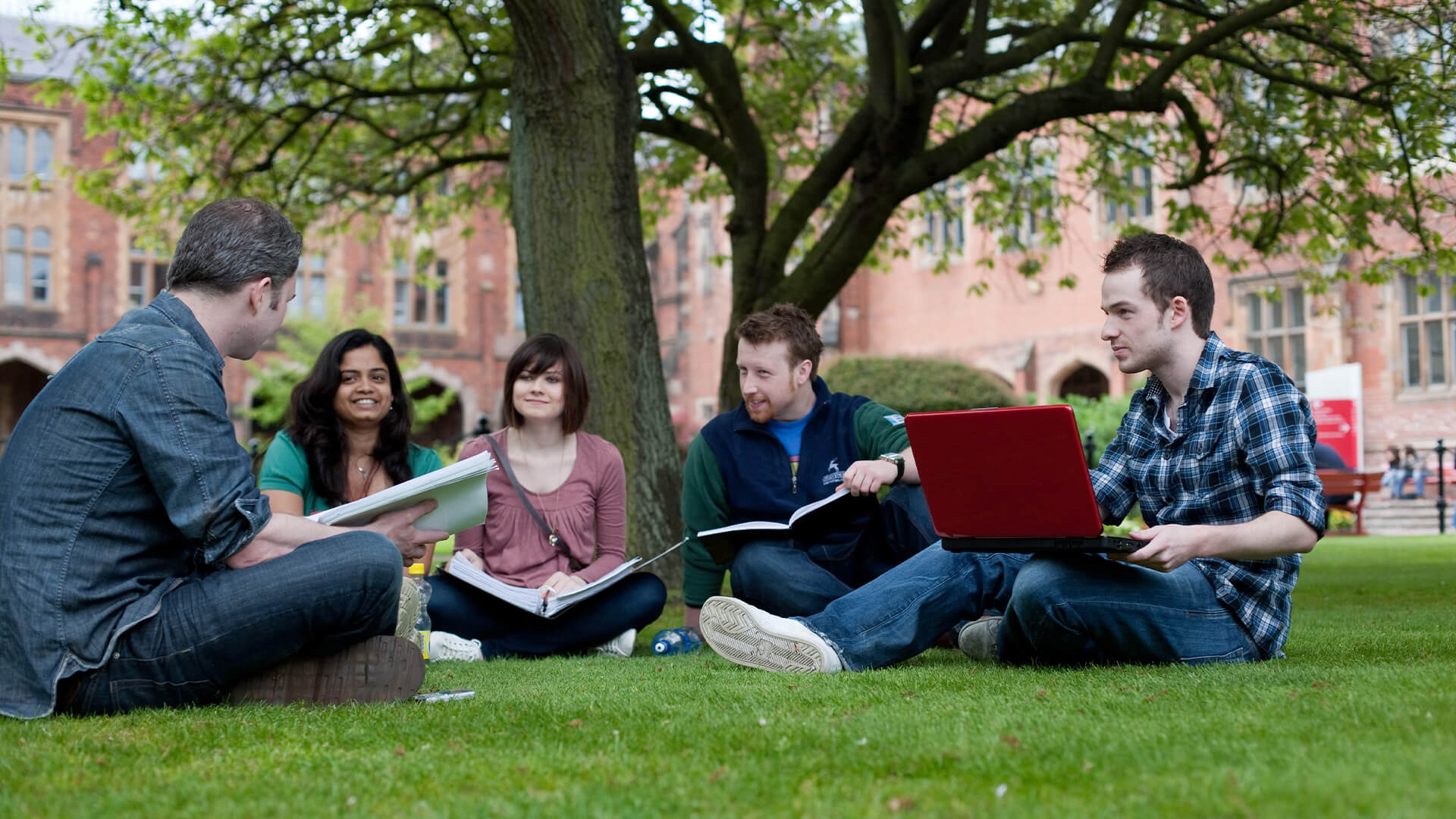 Students  studying on the lawn outside the Lanyon Building at Queen's University Belfast