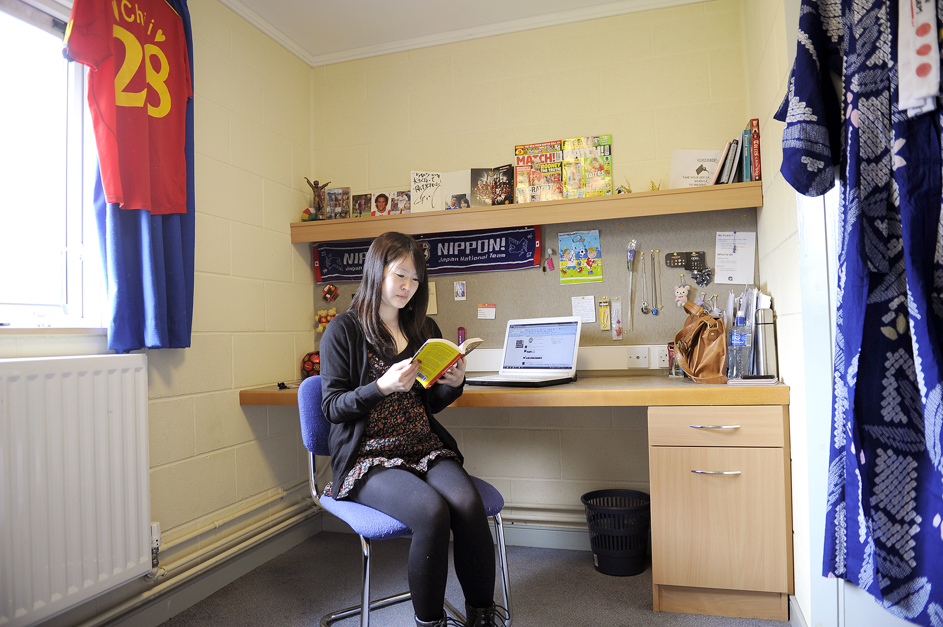Student reading in a private en suite room in Elms BT9 student residences